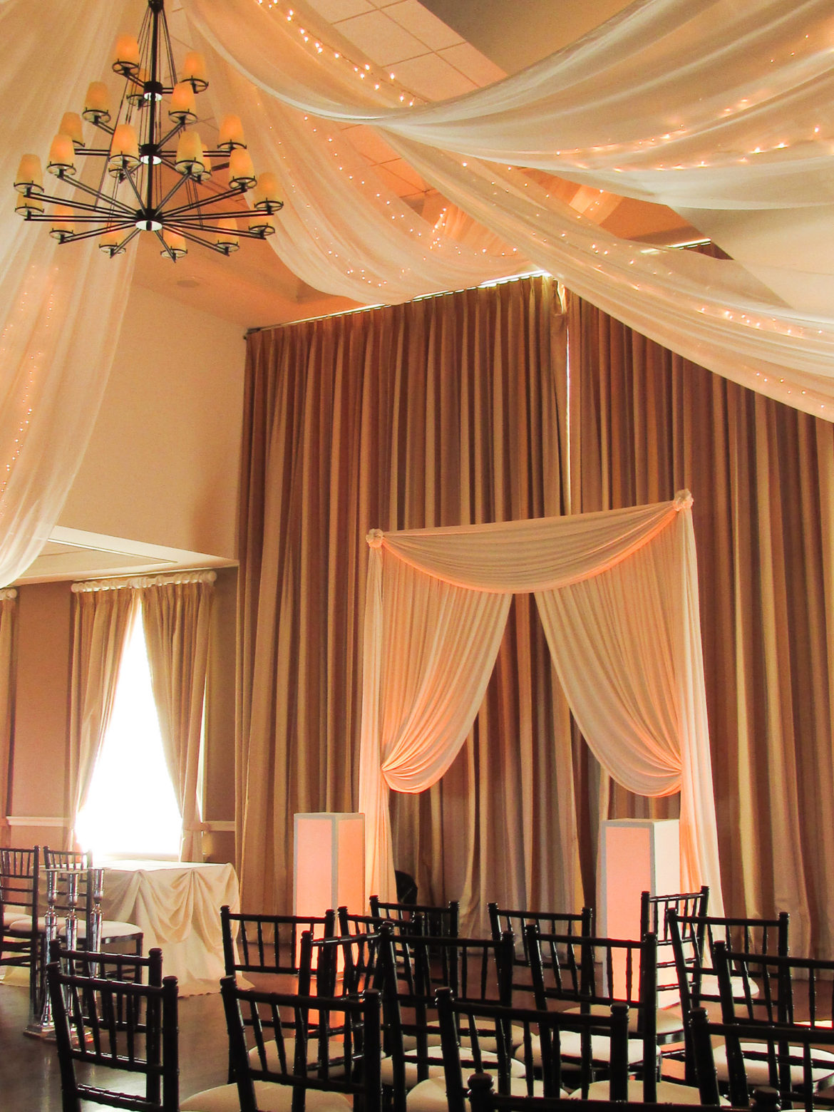 Elegant_Event_Lighting_Chicago_Arrowhead_Golf_Club_Wheaton_Wedding_Ceiling_Drapes_Twinkle_Lights_Ivory_Bridal_Arch_Ceremony_Flower_Pedestal_Amber_Uplighting