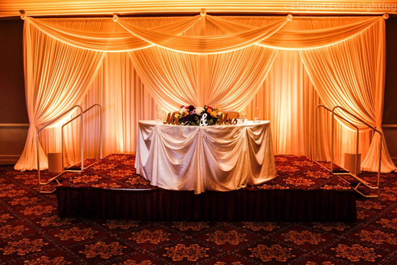 Elegant_Event_Lighting_Chicago_Bolingbrook_Golf_Club_Wedding_Sweetheart_Table_Backdrop_Ivory_Draping_LED_Uplighting_Amber