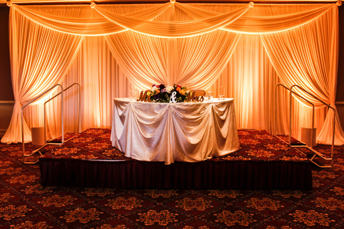Elegant_Event_Lighting_Chicago_Bolingbrook_Golf_Club_Wedding_Sweetheart_Table_Backdrop_Ivory_Draping_LED_Uplighting_Amber