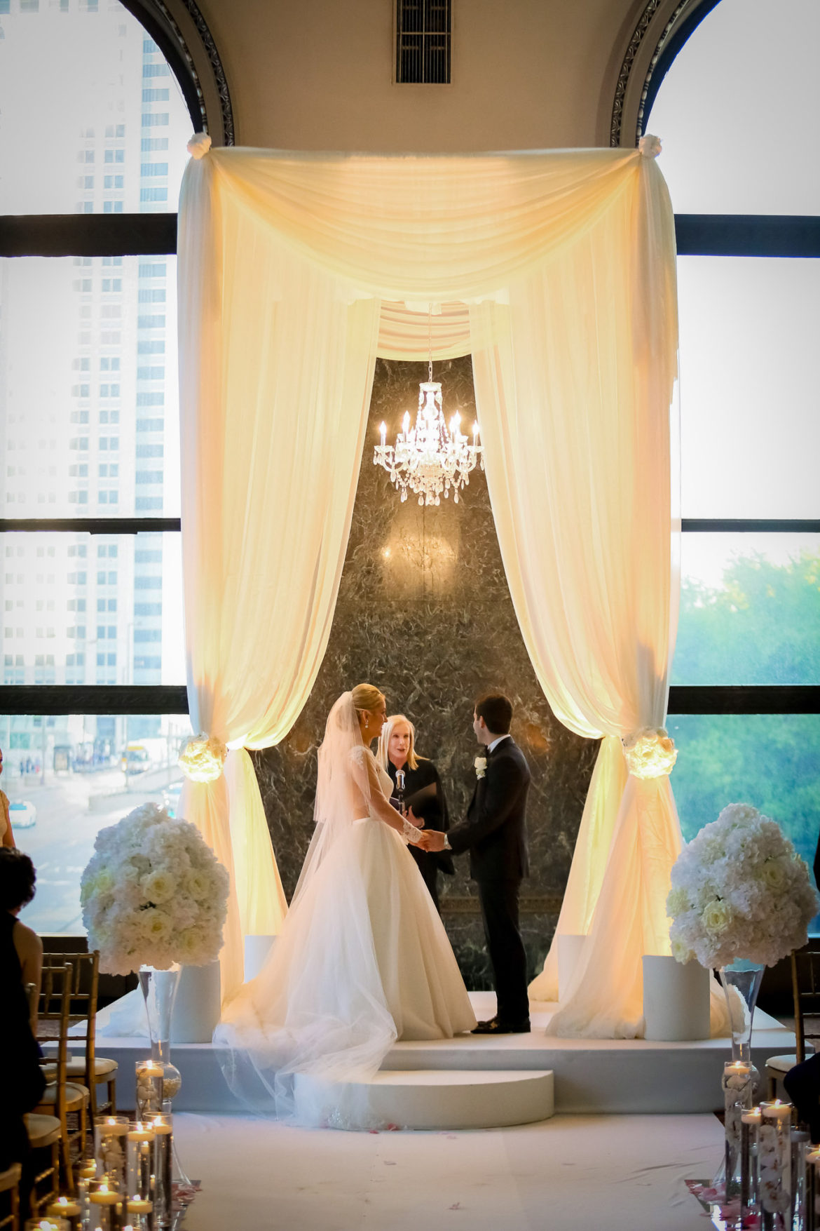 Elegant_Event_Lighting_Chicago_Cultural_Center_GAR_Hall_Wedding_Ceremony_Ivory_Bridal_Canopy_Chuppah_Crystal_Chandelier_Stage_Cover_Aisle_Runner_Elegant