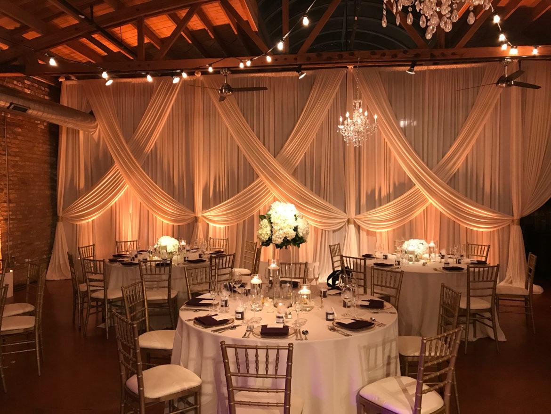 Elegant_Event_Lighting_Chicago_Loft_On_Lake_Wedding_Uplighting_Ivory_Backdrop_Draping_Cafe_Globe_Lights_Crystal_Chandeliers_Flower