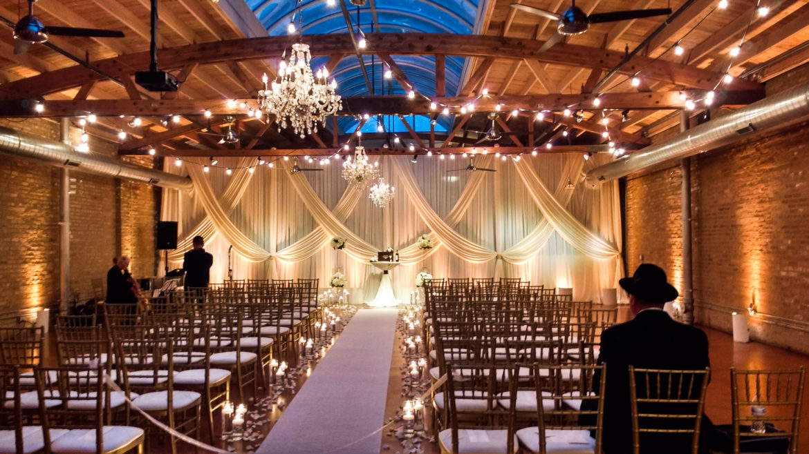 Elegant_Event_Lighting_Chicago_Loft_On_Lake_Wedding_Uplighting_Ivory_Backdrop_Draping_Cafe_Globe_Lights_Crystal_Chandeliers_Flower_Aisle_Runner_Romantic_Rustic