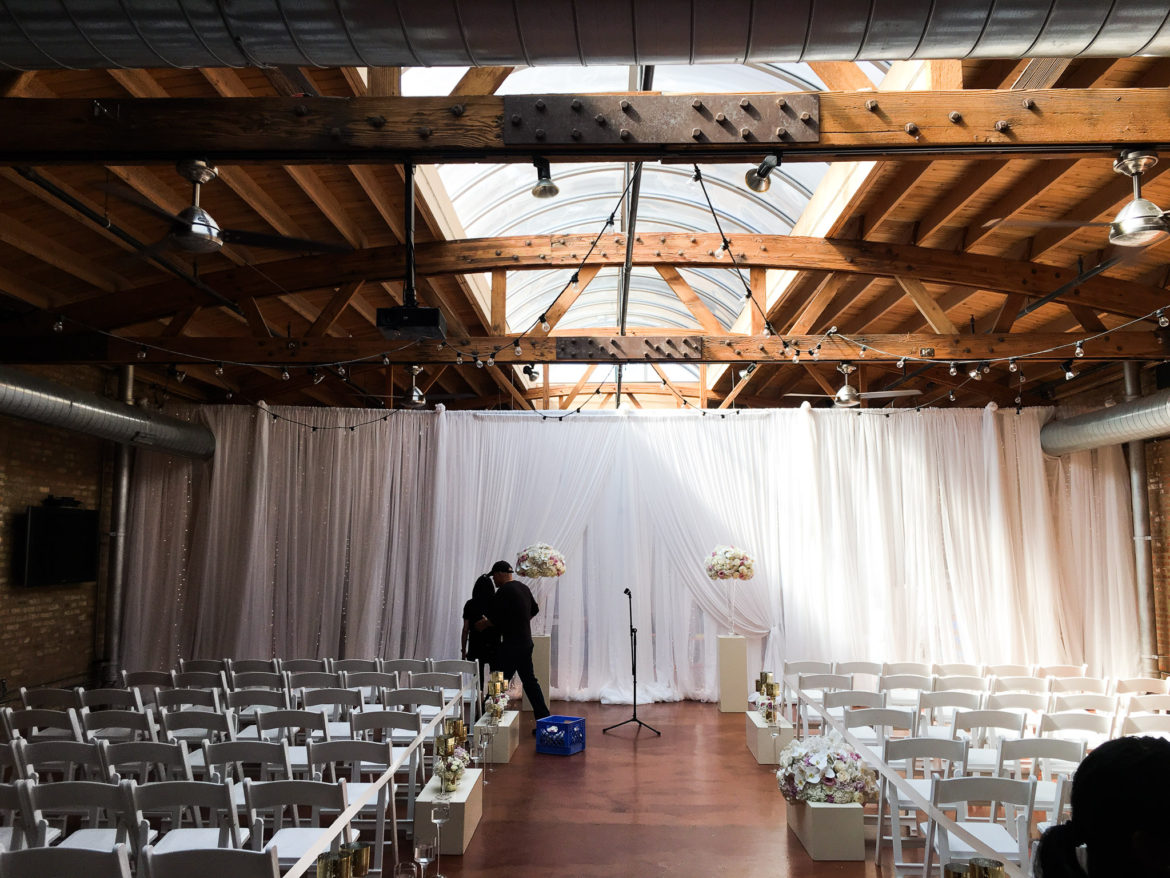 Elegant_Event_Lighting_Chicago_Loft_On_Lake_Wedding_White_Backdrop_Draping_Twinkle_String_Lights_Cafe_Globe_Lighting_Flower