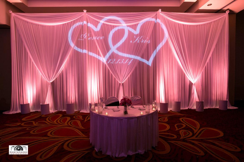Elegant_Event_Lighting_Chicago_Marriott_Schaumburg_Wedding_Sweetheart_Table_Backdrop_White_Draping_Pink_Uplighting_Monogram